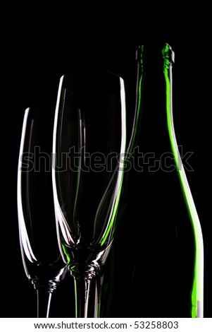green glass bottle of wine and wineglasses on black background