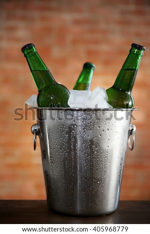 Green glass bottles of beer in ice-pail on brick wall background - stock photo