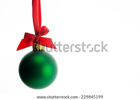 Green glass Christmas ball ornament tied with a red ribbon.