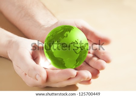green glass globe in hand - stock photo