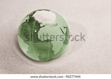 Green Glass globe on sand background - stock photo