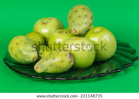 Green glass platter filled with variety of green fruit against green background.  Apples, cactus pear and lime. - stock photo