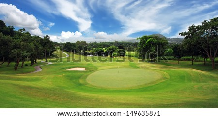 green golf course and blue sky  - stock photo