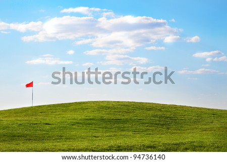 Green golf course with flag in the summer time - stock photo