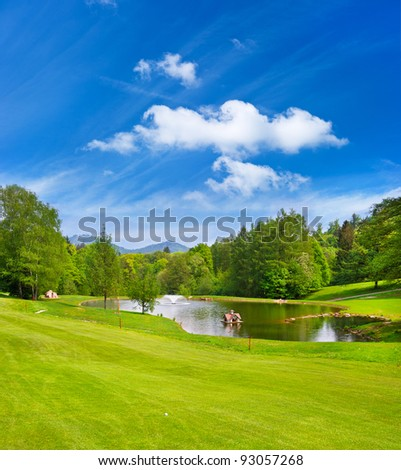 green golf field with blue sky. european golf course landscape - stock photo