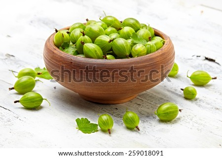 green gooseberries in a ceramic bowl on an old wooden table - stock photo