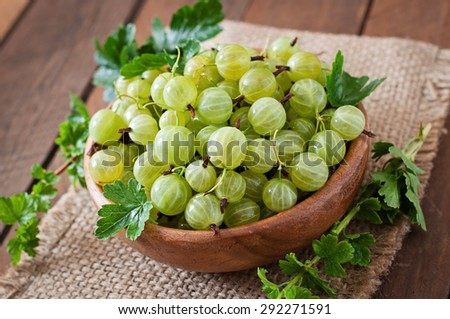 Green gooseberries in a wooden bowl - stock photo