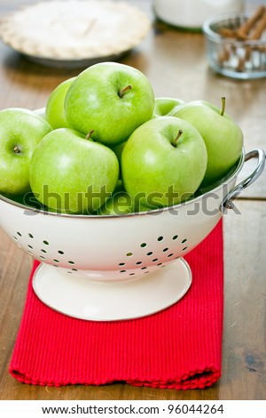 Green granny smith apples in a colander with apple pie sugar and cinnamon sticks in the background. - stock photo