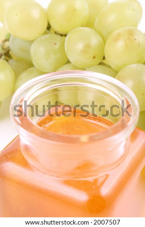 green grapes and jar of honey isolated on white