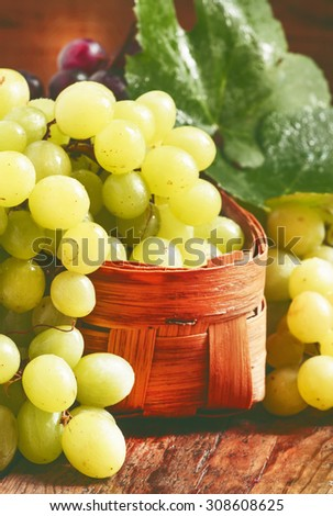 Green grapes in a wicker basket in a rustic style, selective focus