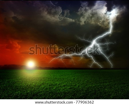 Green grass against a stormy sky - stock photo