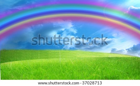 green grass and a blue sky with a rainbow - stock photo