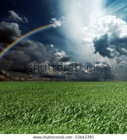 green grass and blue cloudly sky with rainbow - stock photo