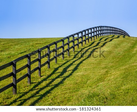 Green Grass And Blue Sky Along A Fence Line And Pasture During Autumn In Horse Country, Lexington, Kentucky, USA - stock photo