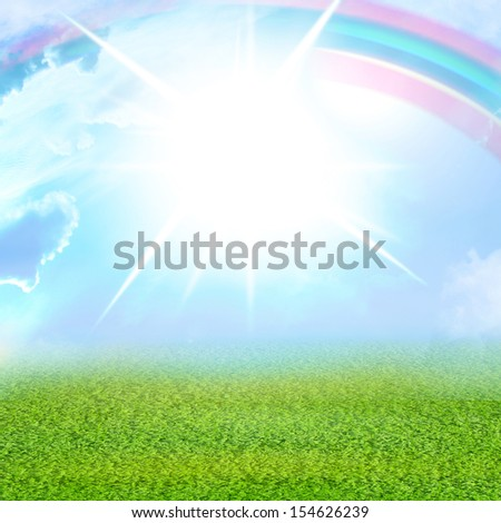 green grass and blue sky with intense sunlight and a rainbow - stock photo