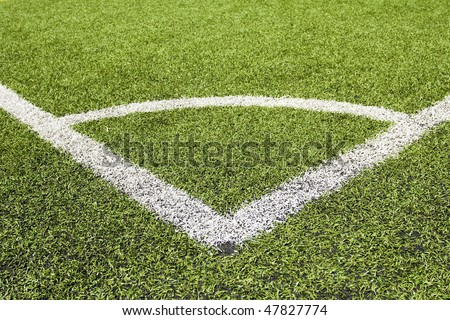 Green grass and corner lines of an outdoor football field (artificial covering) - stock photo