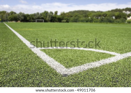 Green grass and corner lines of an outdoor football field (artificial covering) - blured at background - stock photo