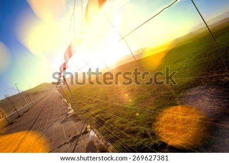 Green grass and fence.Abstract sunset landscape.Flare lights and defocus - stock photo