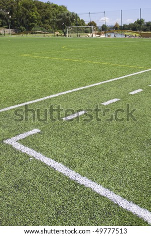 Green grass and sport lines painted at an outdoor playing field (artificial covering) - stock photo
