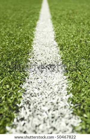 Green grass and sport lines painted at an outdoor playing field (artificial covering) - photographed with shallow DOF - stock photo