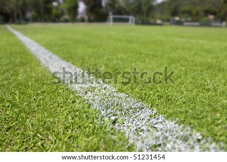 Green grass and sport lines painted at an outdoor playing field (artificial covering). Photographed with shallow DOF - stock photo