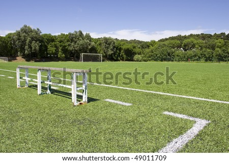 Green grass and sport lines painted at an outdoor playing field with side bank - stock photo