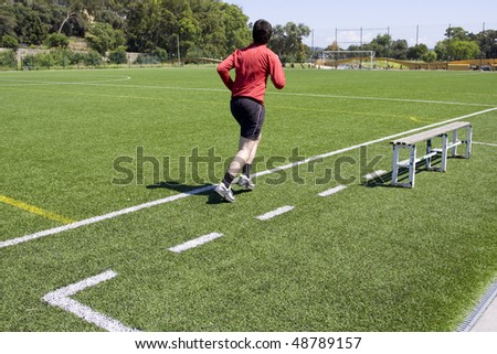 Green grass and sport lines painted at outdoor playing field with a man running