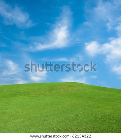 Green grass and the sky with clouds - stock photo
