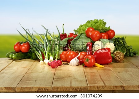 green grass blue sky and fresh vegetables on top  - stock photo