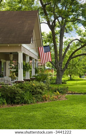 green grass, blue sky and old house with american flag
