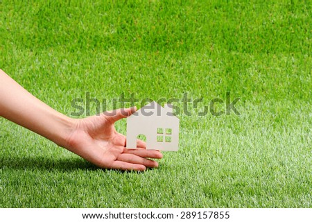 Green grass, house and human hand