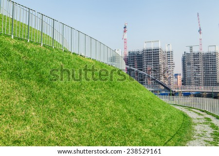 Green grass in park with construction site  - stock photo