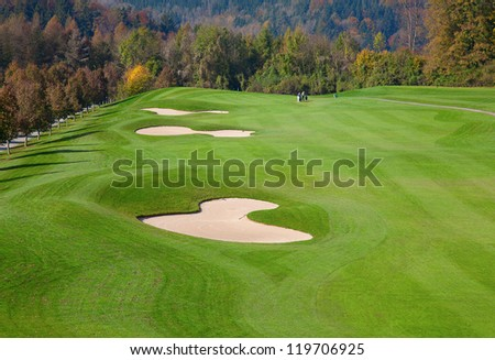 green grass of the golf course surrounded by autumnal forest - stock photo