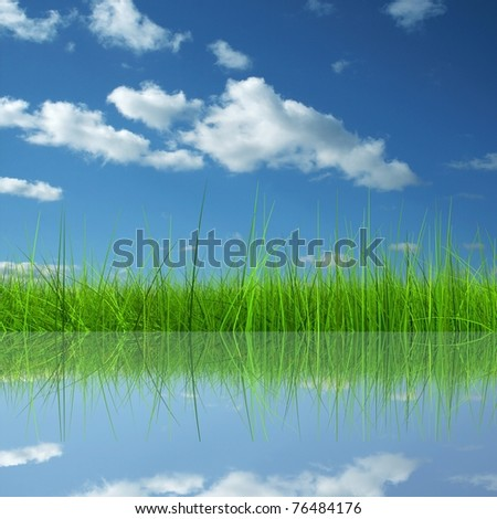Green grass over a blue sky background and reflection in water - stock photo