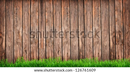 green grass over wood fence background - stock photo