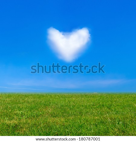 Green grass under blue sky and a heart shape cloud. Beauty nature background - stock photo