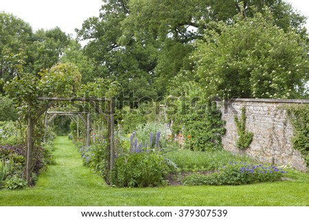Green grass walking pathway between autumn color leaves high hedge, ending with a gate, in an English garden . - stock photo