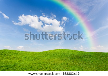 Green grass with blue sky and rainbow as background  - stock photo