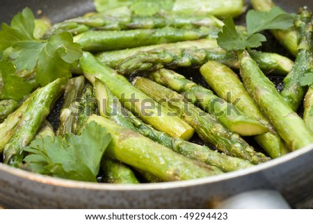 Green grilled asparagus in a frying pan - stock photo