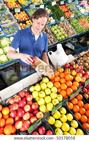 Green grocer putting red apples in a brown paper bag - stock photo