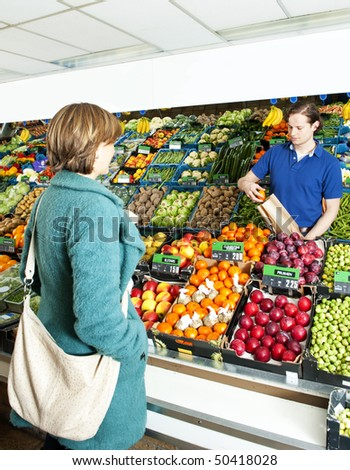 Green grocer serving a customer behind the display counter in his shop, putting apples in a paper bag - stock photo