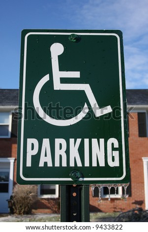 Green handicapped parking sign with icicles. - stock photo