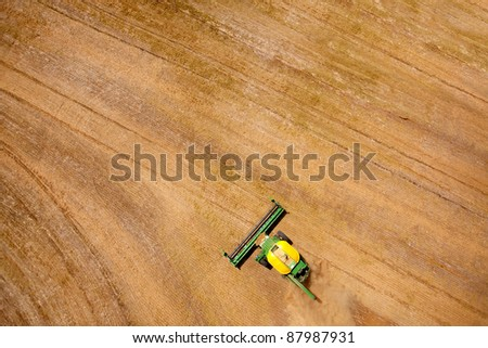 Green harvester in a lentil field creating an abstract background texture - stock photo
