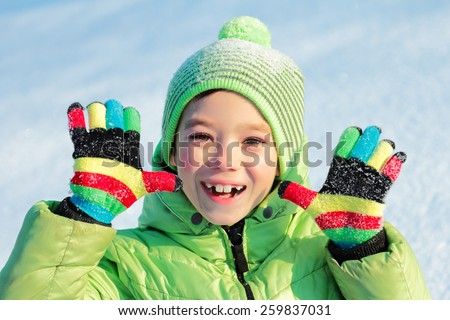 Green hat and jacket clothing boy with colorful gloves on snow background - stock photo