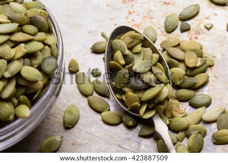 green healthy pumpkin seeds on steel plate with spoon