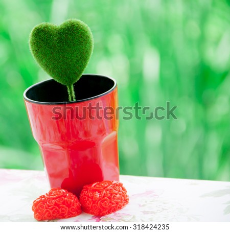 Green heart in the red cup - stock photo