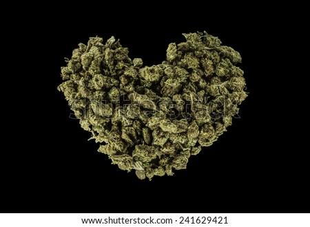 Green heart made of marijuana isolated on a black background  - stock photo