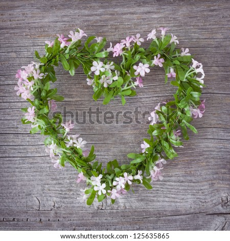Green heart on wooden background - stock photo