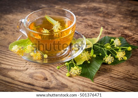 Green herbal tea with linden flowers on old wooden table