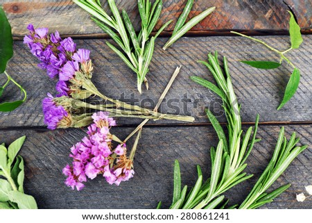 Green herbs and leaves on wooden  table, top view - stock photo